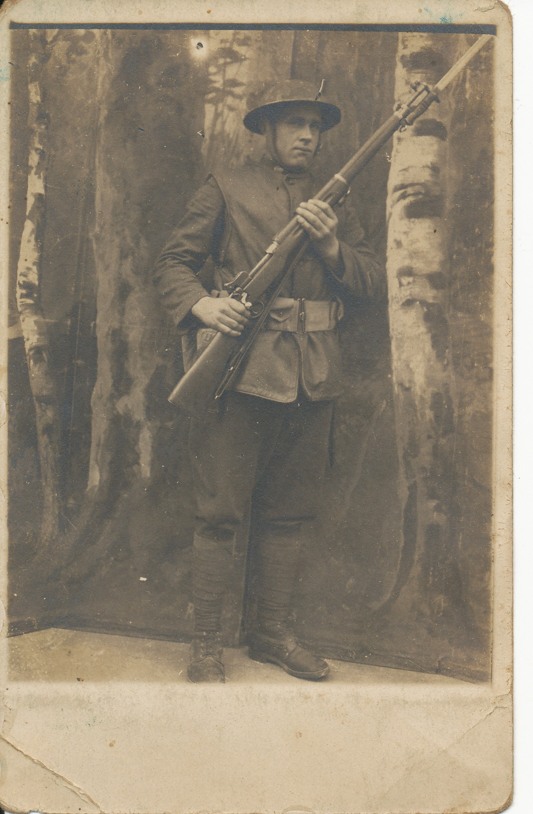 black and white portrait of man in uniform standing holding a gun