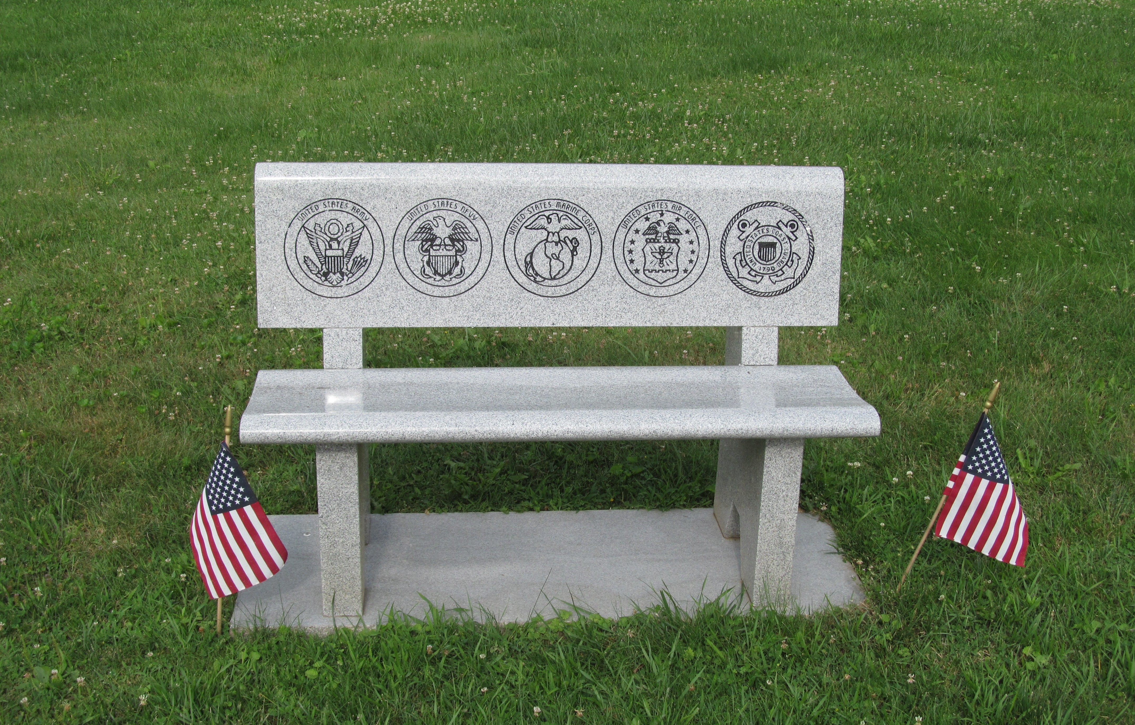 detail of carved granite bench with symbols of five military branches