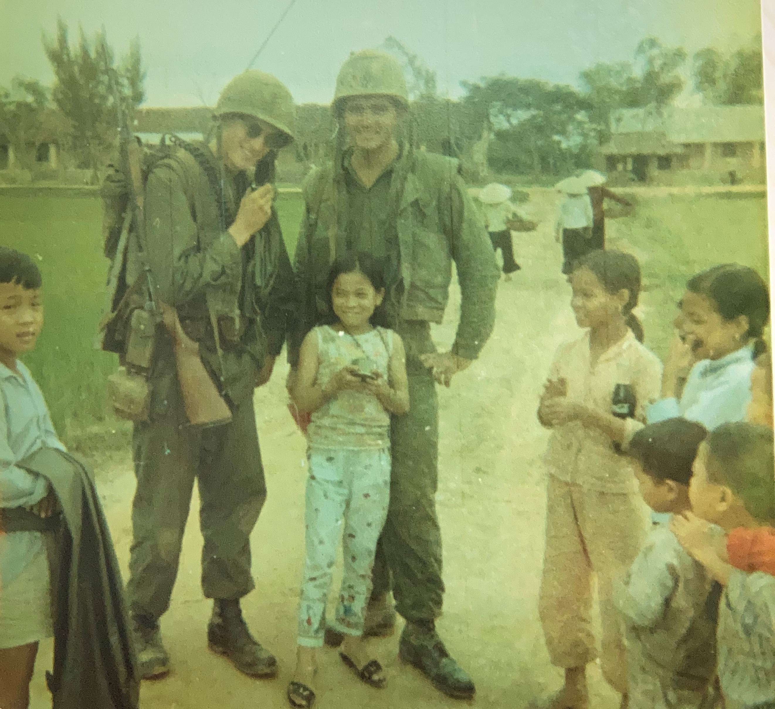 Color photo of two soldiers and several children in Vietnam