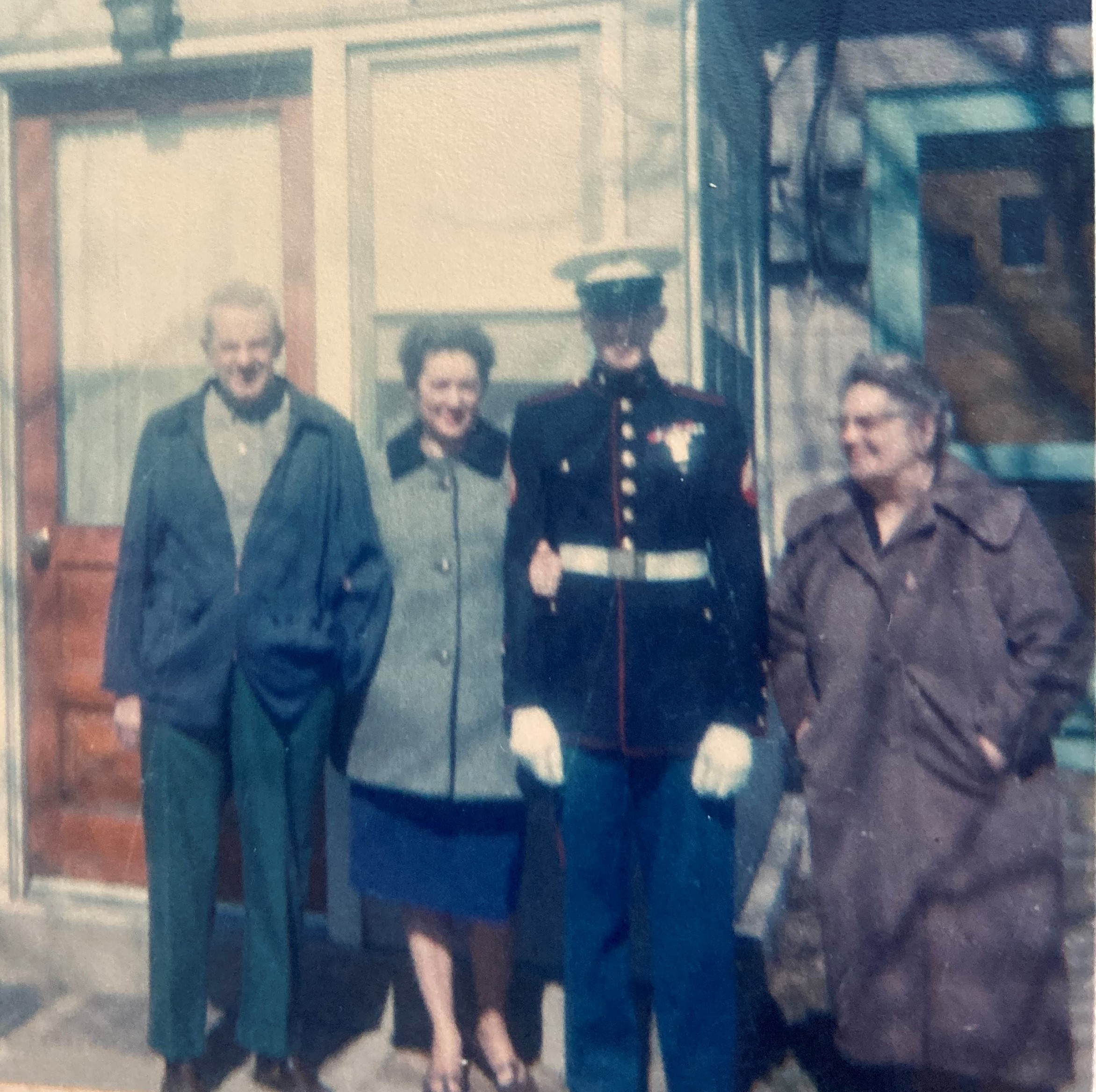 color photo of young man in uniform standing with 2 older women and an older man