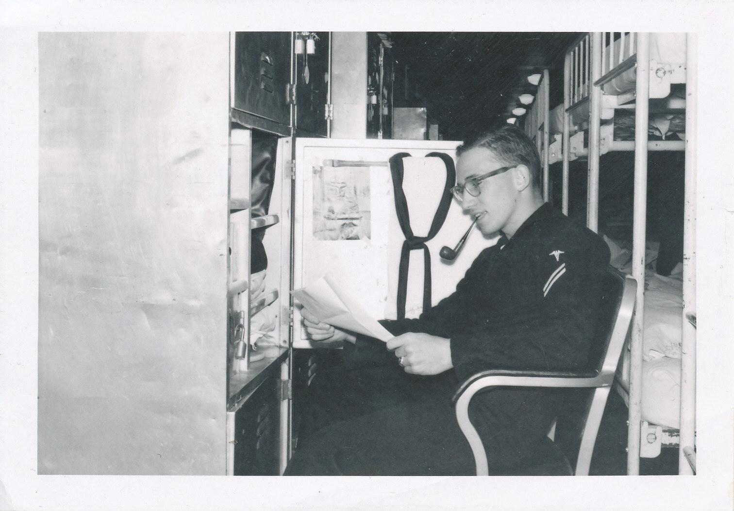 black and white photo of navy man sitting and smoking a pipe