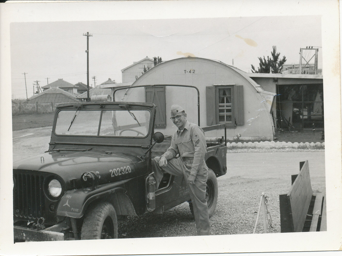 young soldier standing with one foot on a jeep