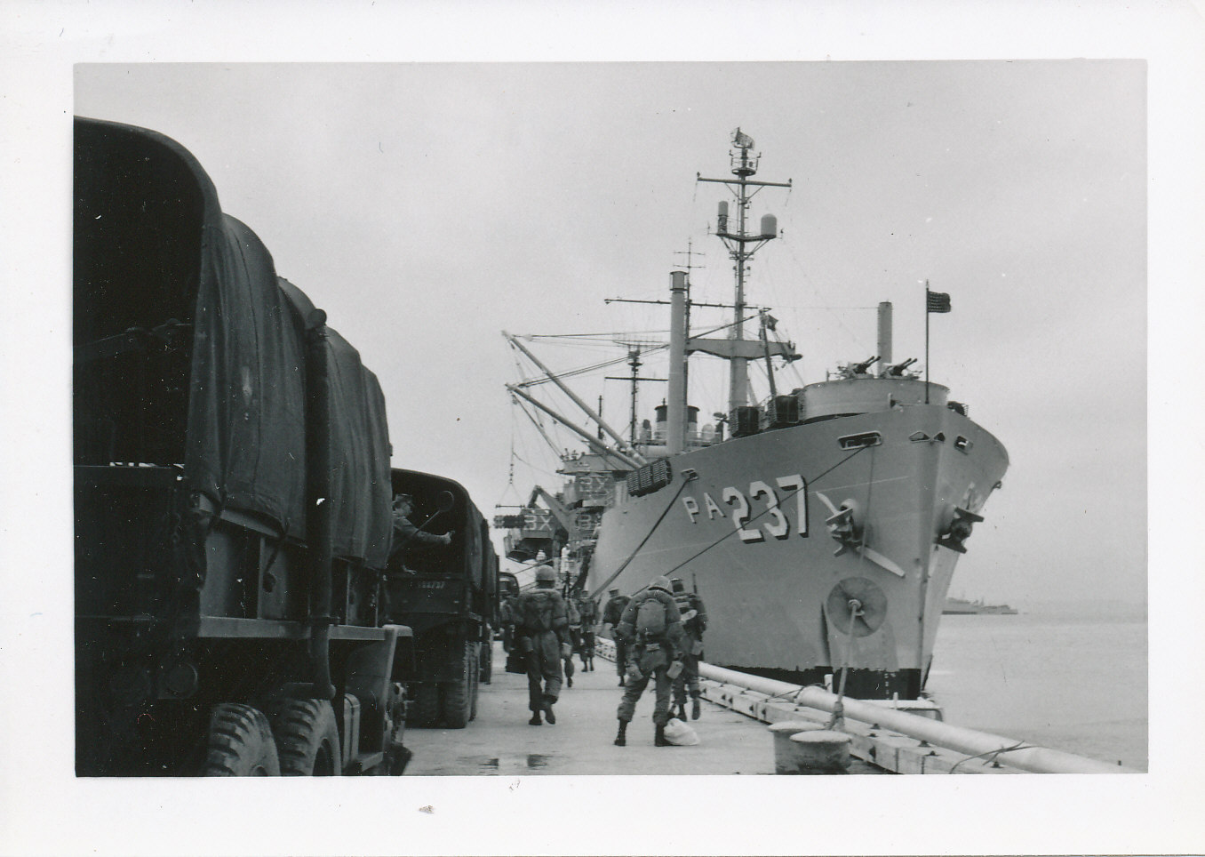 soldiers walking between a line of jeeps and a navy ship