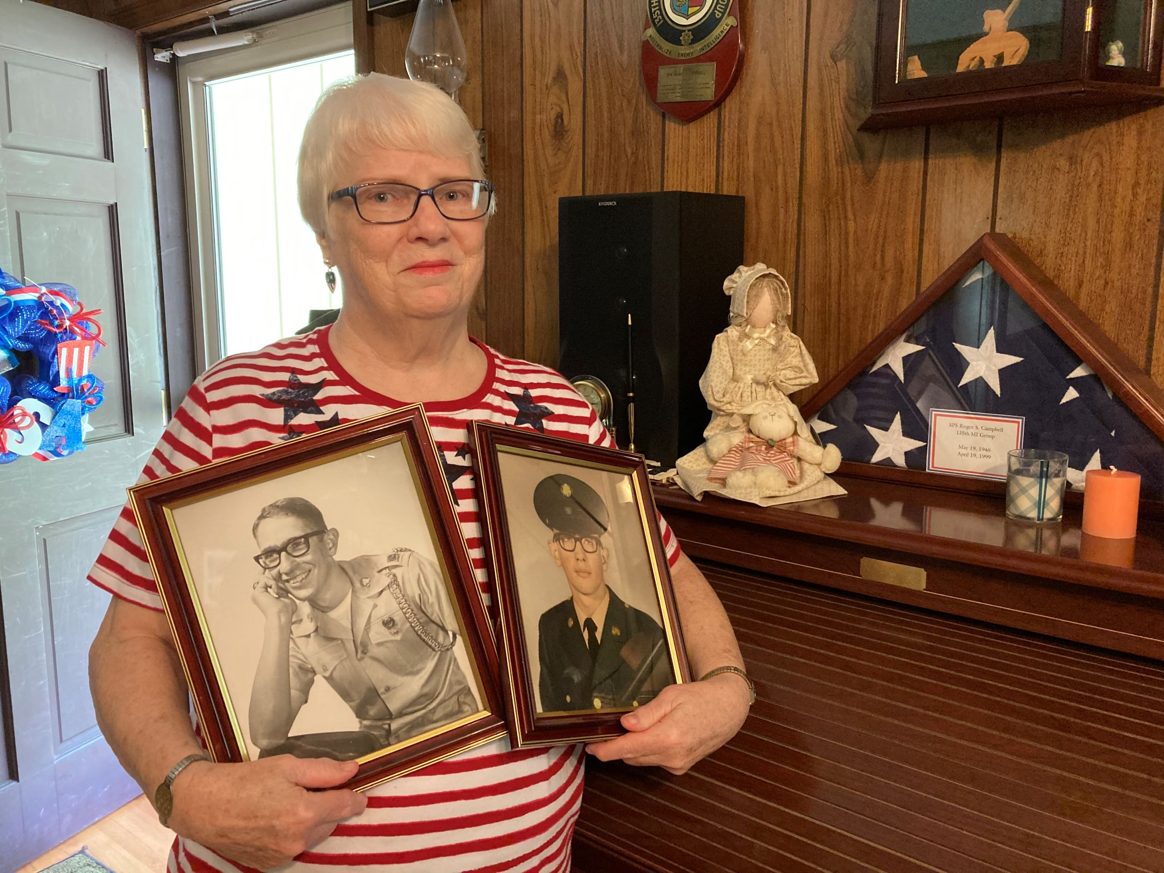 woman holding two framed photos
