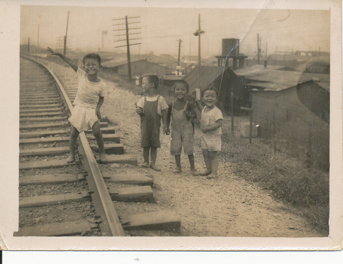 Black and white photo of kids standing near railroad tracks