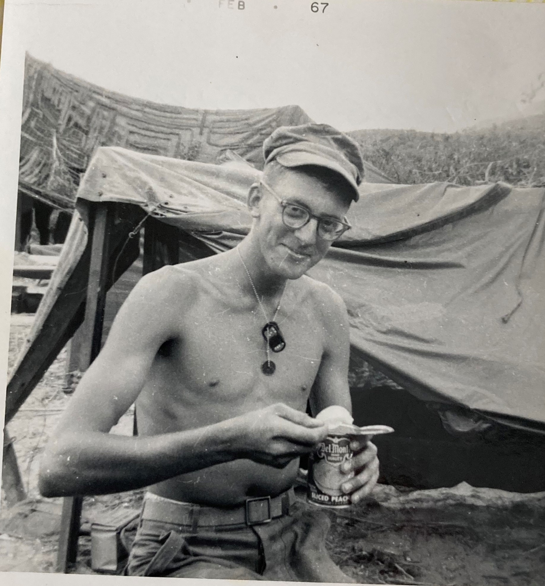 smiling young soldier holding an open can of food