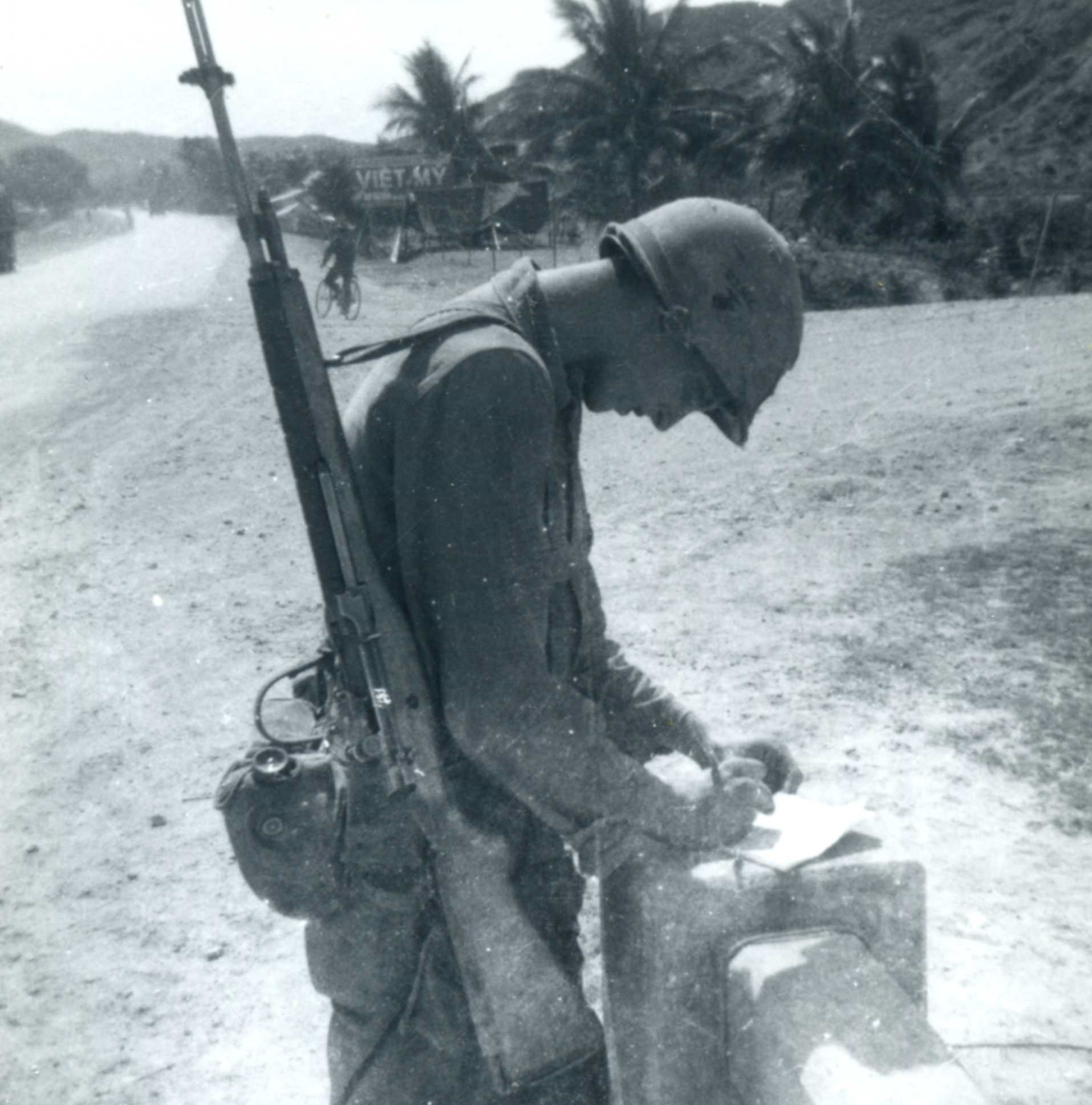 black and white photo of soldier in uniform writing