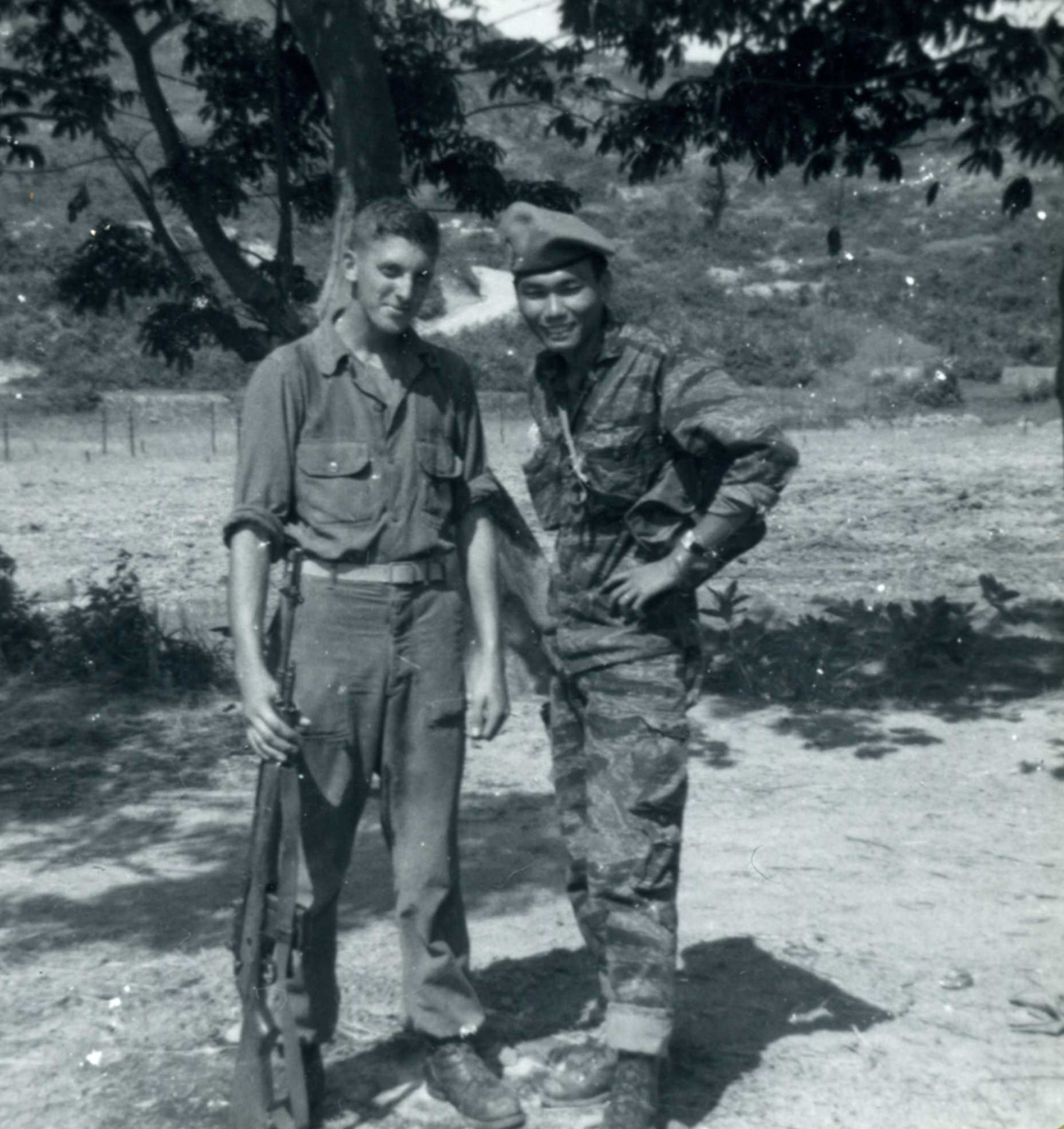 black and white photo of two men standing in front of a tree