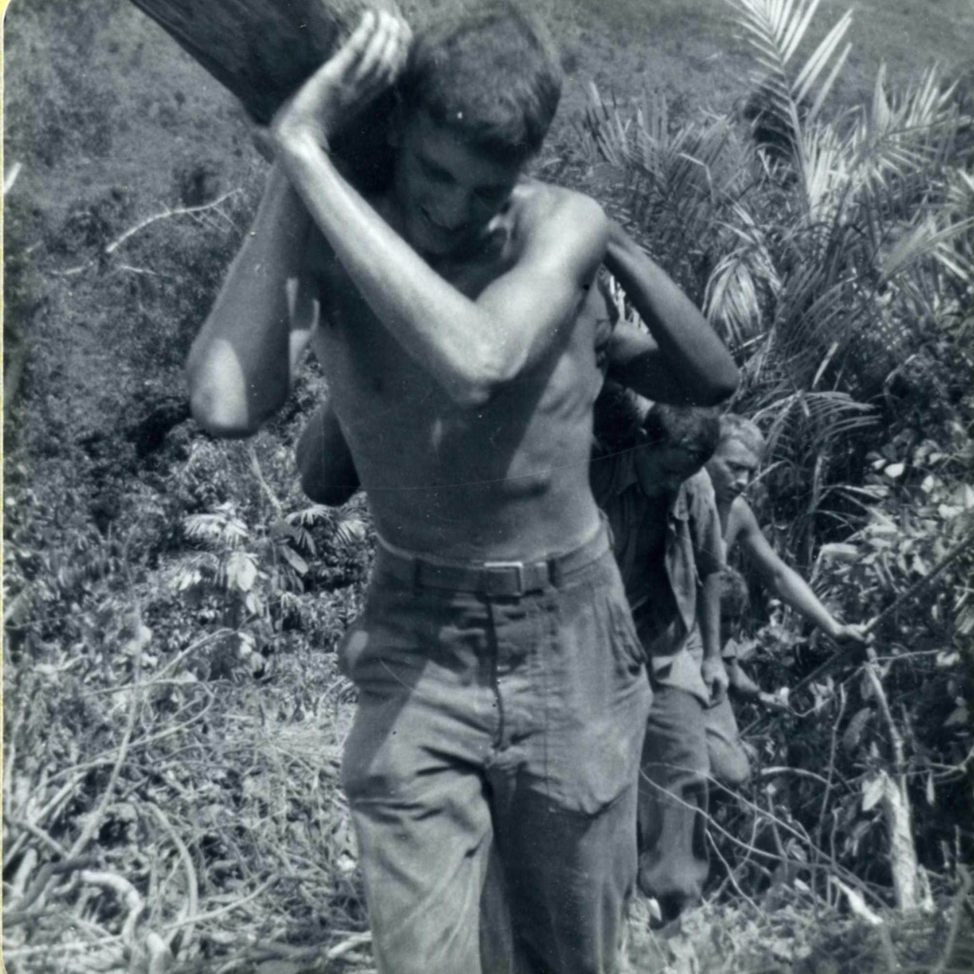 black and white photo of soldier carrying logs