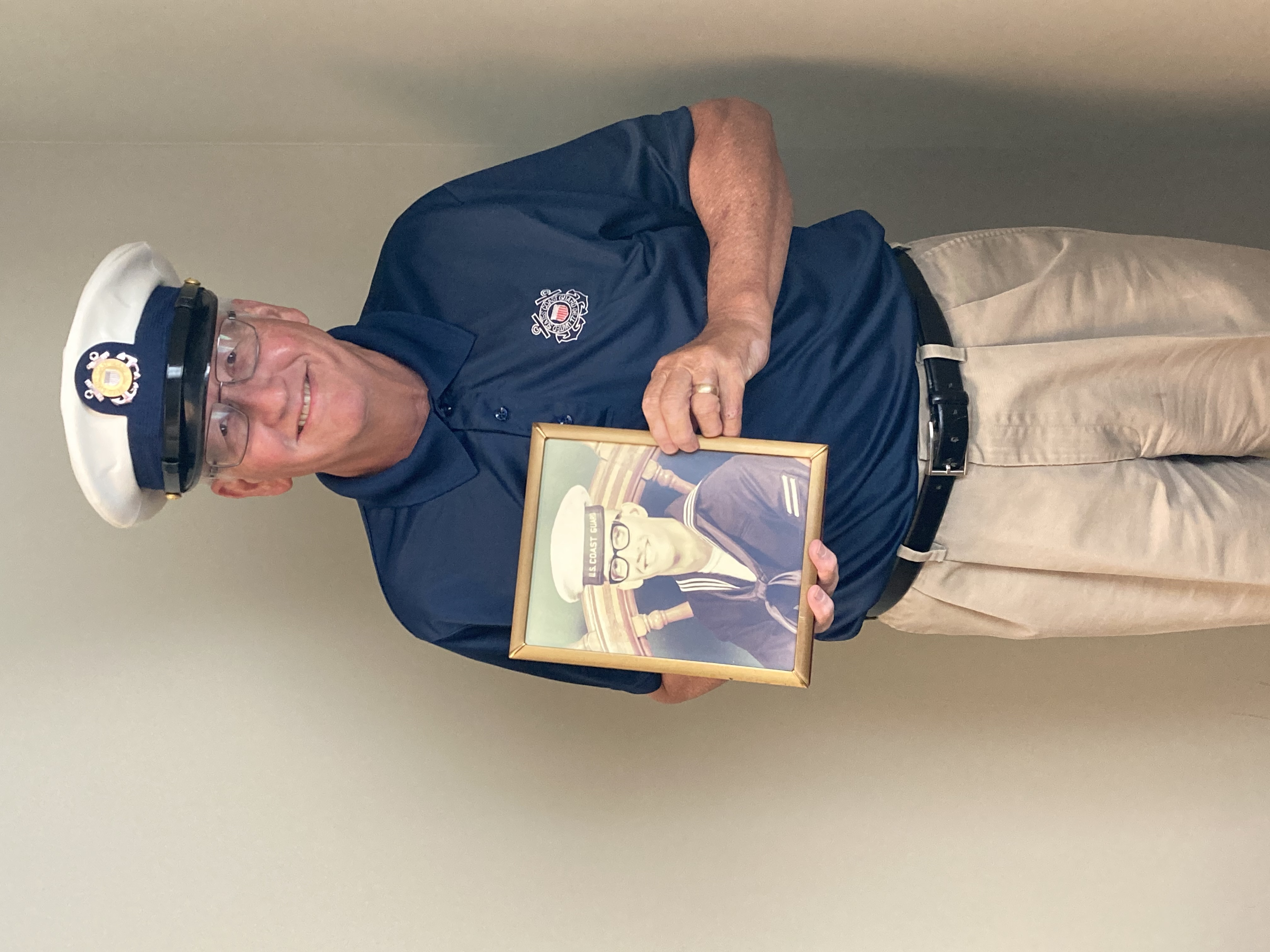 Color photo of Phil Holland holding the older photo of himself