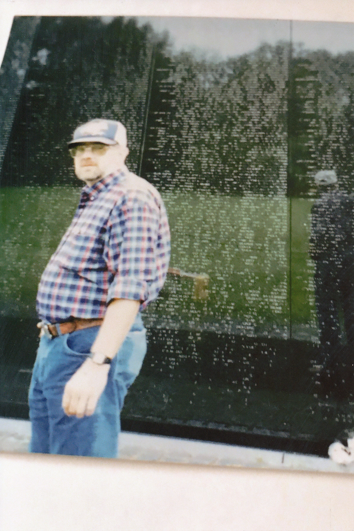 color photo of man standing in from of Vietnam Memorial