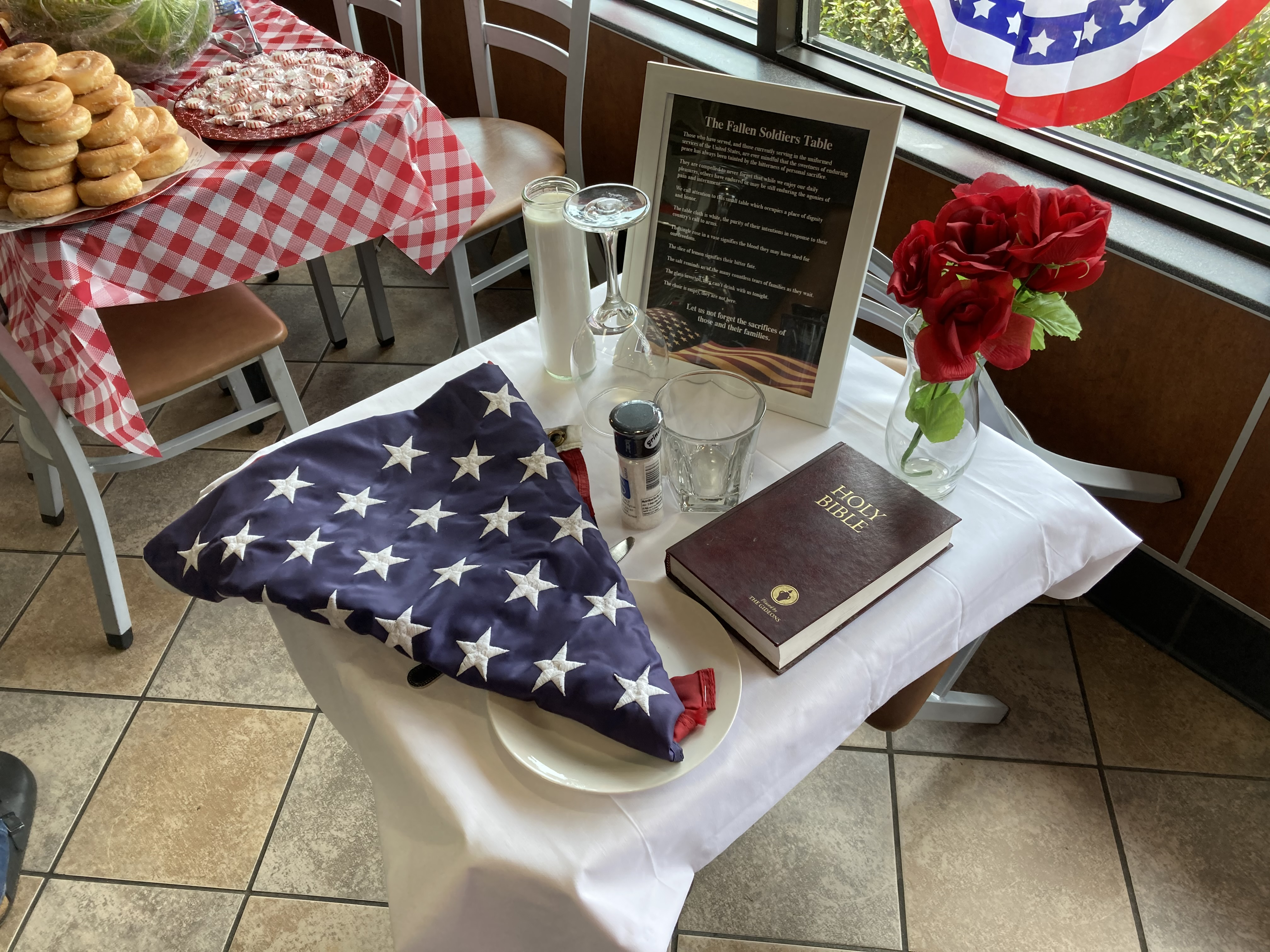 small table with Bible, flowers and an American flag