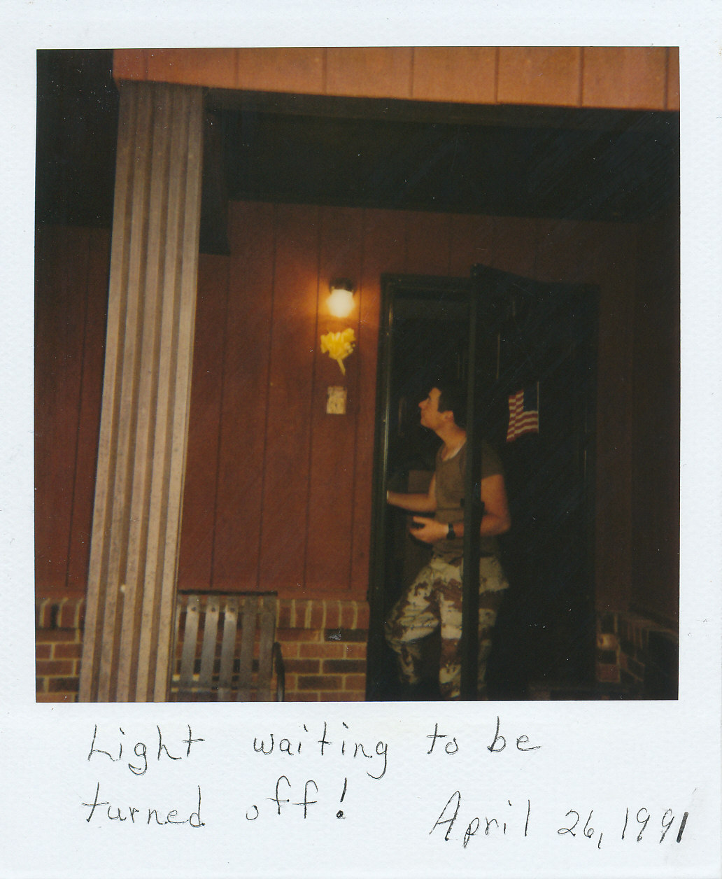 A young man wearing fatigues standing on the front porch of a home
