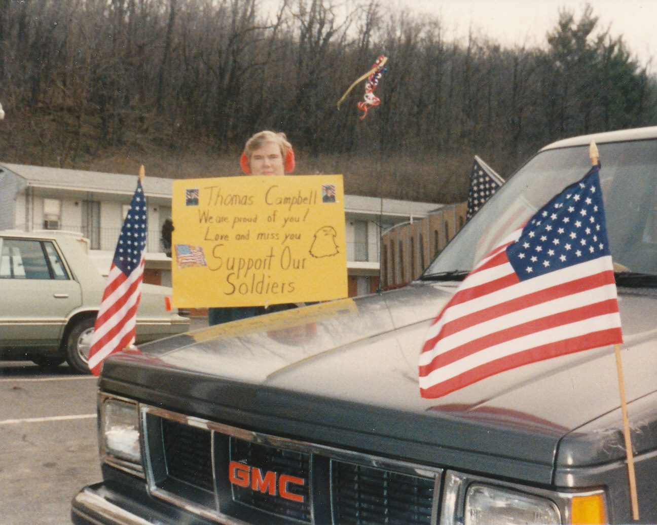 Woman standing behind a truck holding a homemade sign