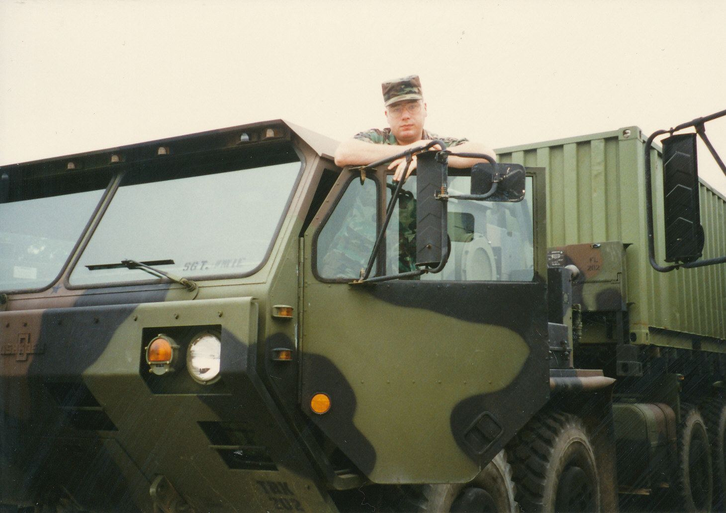 young man in fatigues standing in the door of an army truck