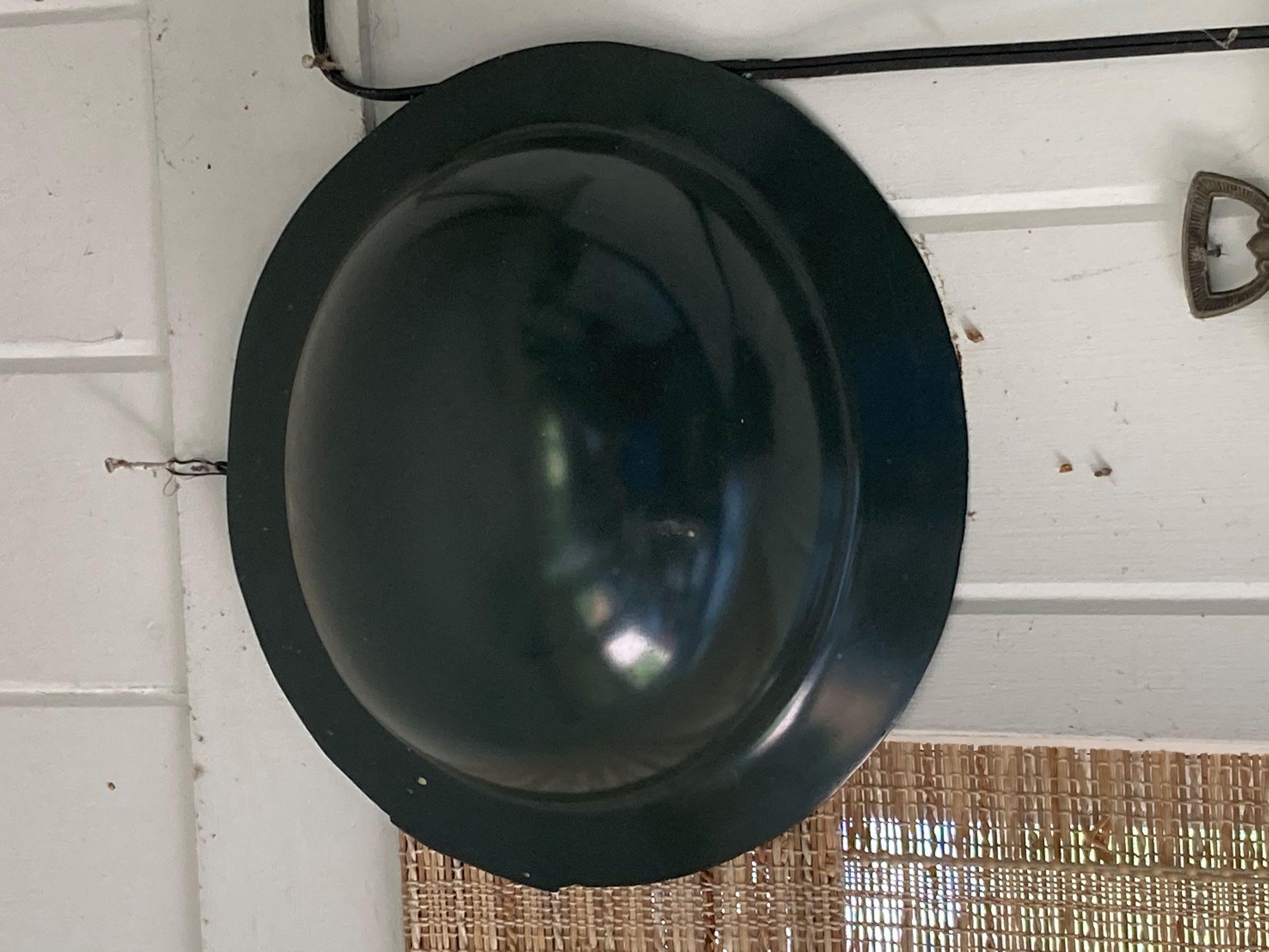 black metal helmet hanging from a door