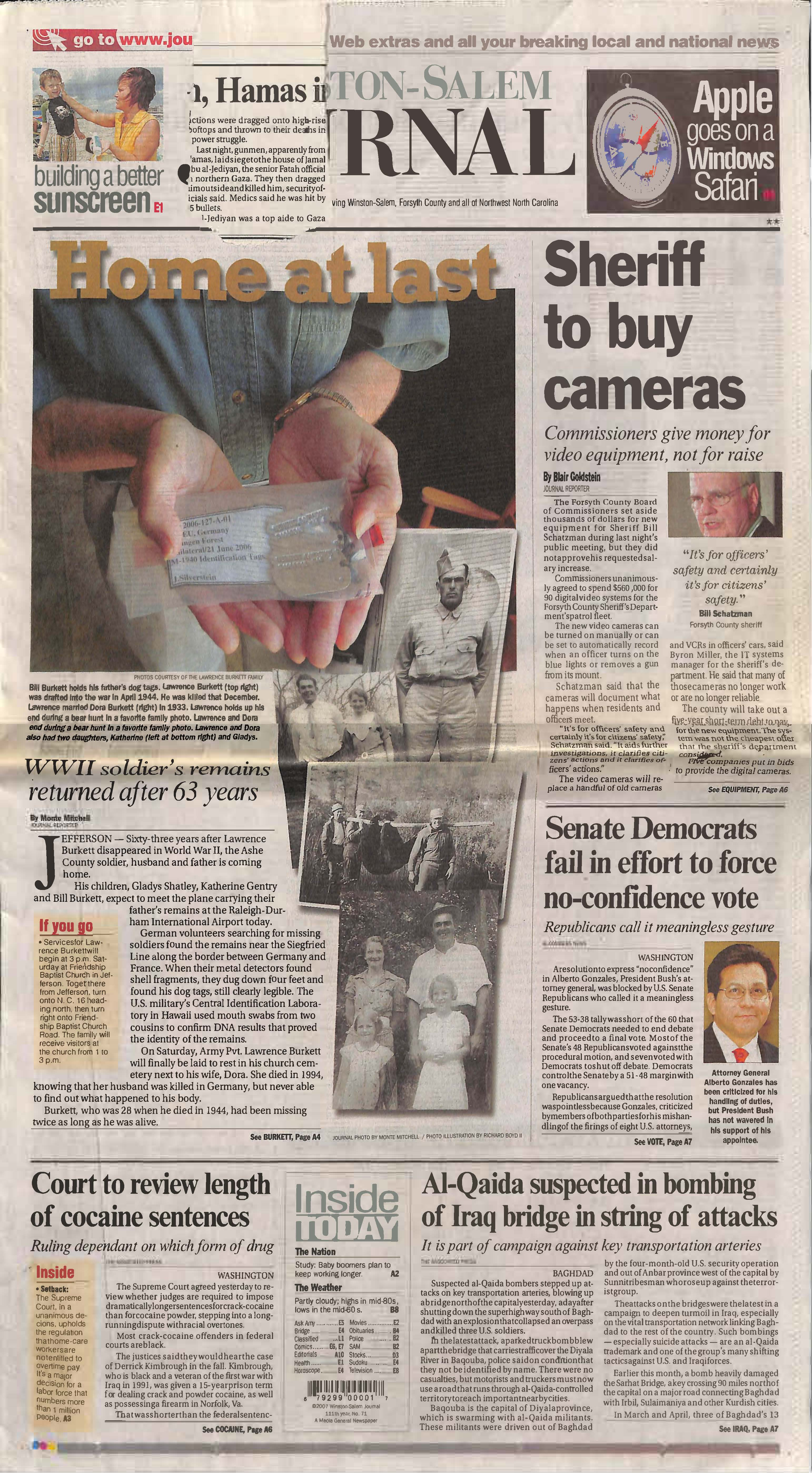 front page of newspaper featuring photo of hands holding soldier's dog tags