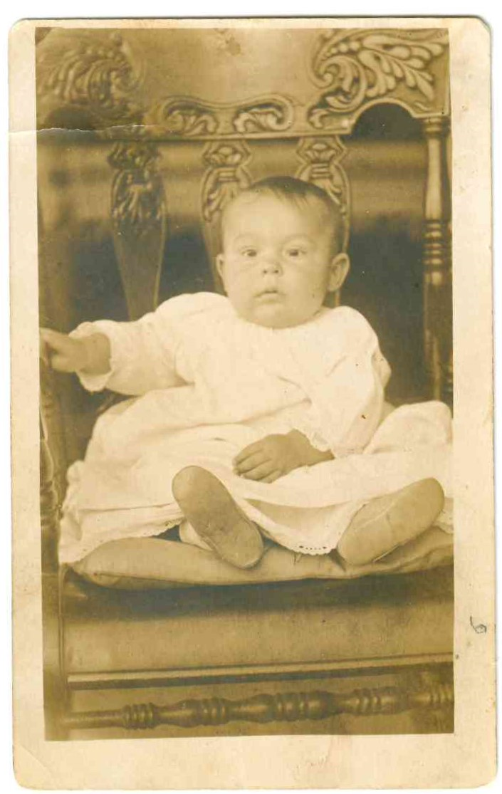 black and white photo of infant sitting in a chair
