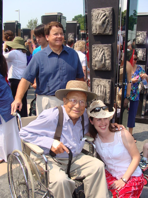 photo of young woman kneeling beside older man in a wheelchair