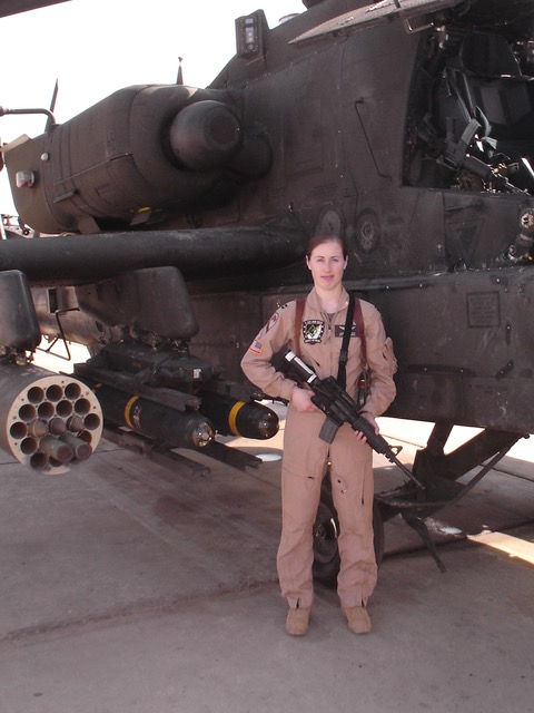 photo of woman in fatigues holding a gun next to a helicopter