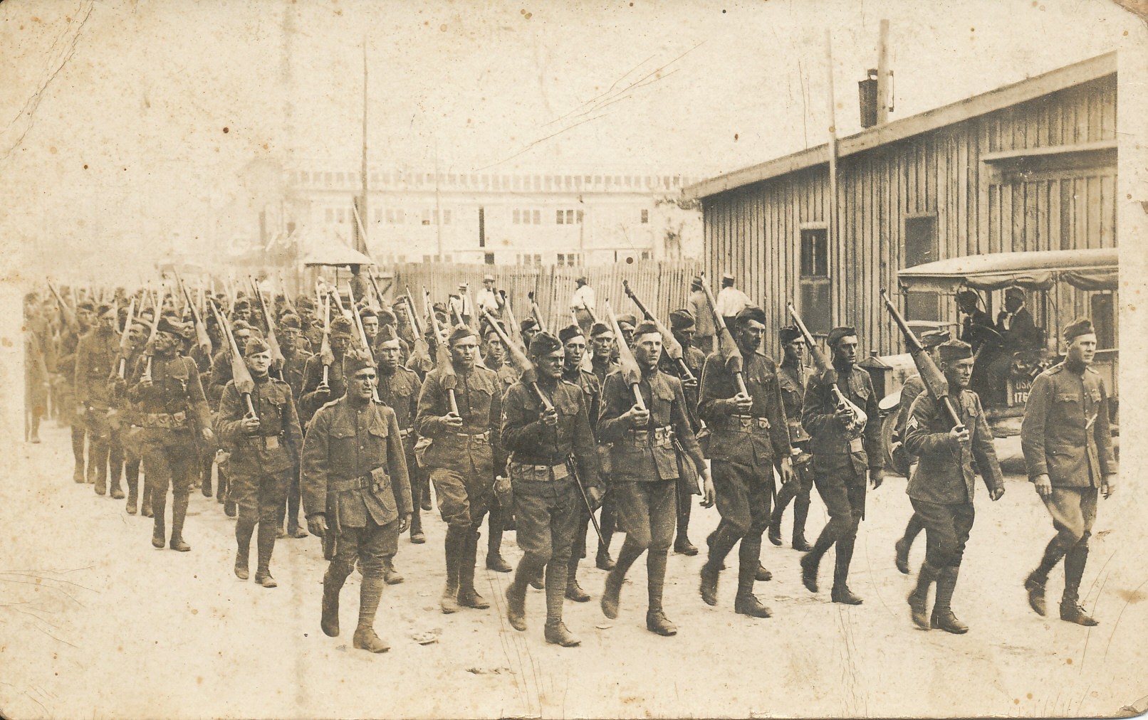 black and white photo of men marching with long guns
