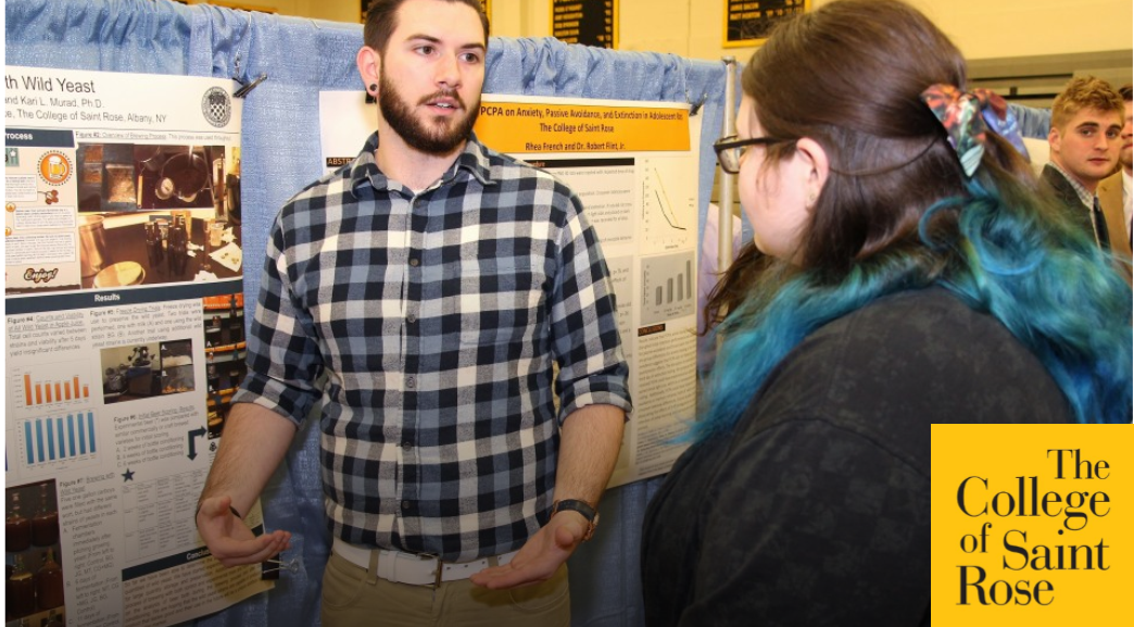 Photo of student presenting their poster at research symposium