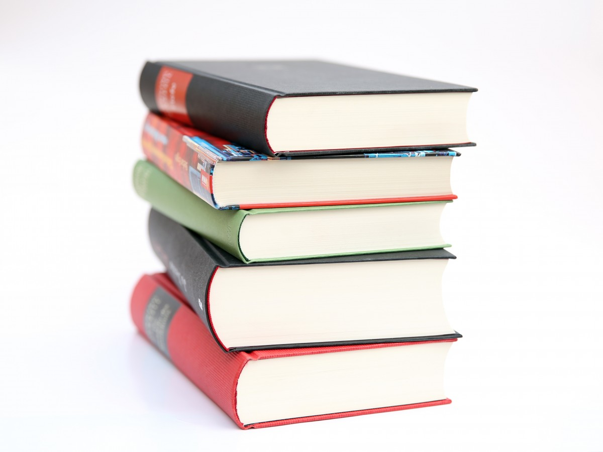 stack of five colorful books with a blank background