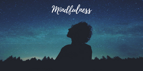 woman looking at night sky with the word mindfulness