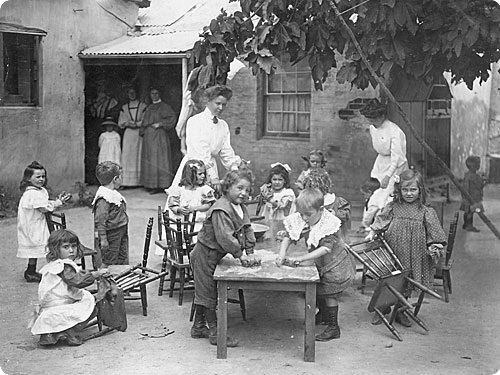 A photo of kindergarten children being taught by two teachers outside the Free Kindergarten in Adelaide.