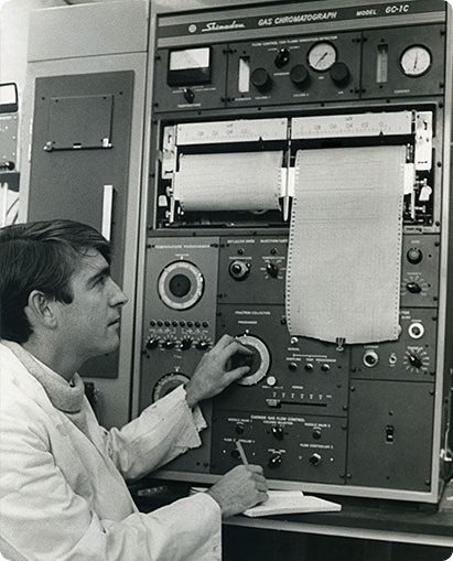 A photo of a scientist operating a gas chromatograph.