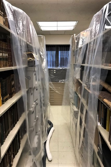 Plastic sheeting and absorbent booms (on floor) used to protect stacks during a small water leak in Special Collections.
