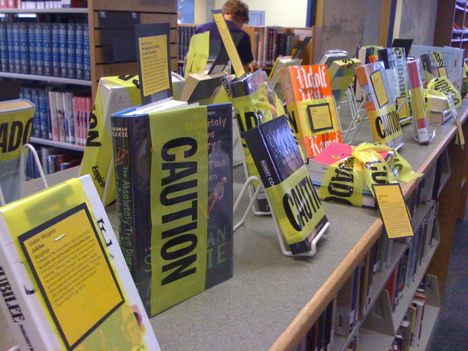 A photograph of a library display featuring books covered in police caution tape.