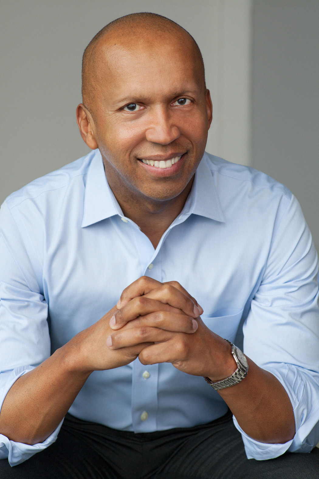 Bryan Stevenson sits with hands clasped in fronto of him.  He is wearing a blue button-down shirt and gray pants.