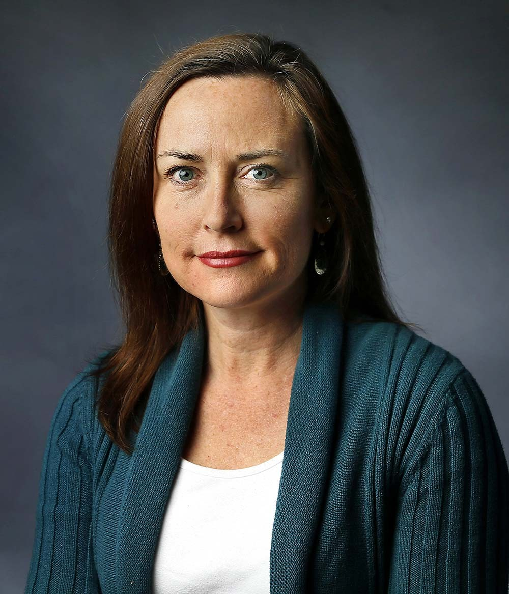 Author photo of Jennifer Berry Hawes.  She has brown hair just past her shoulders and is wearing a green sweater and white shirt.