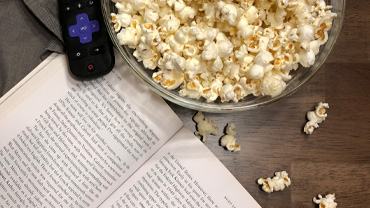 An open book, a remote and some popcorn in a bowl