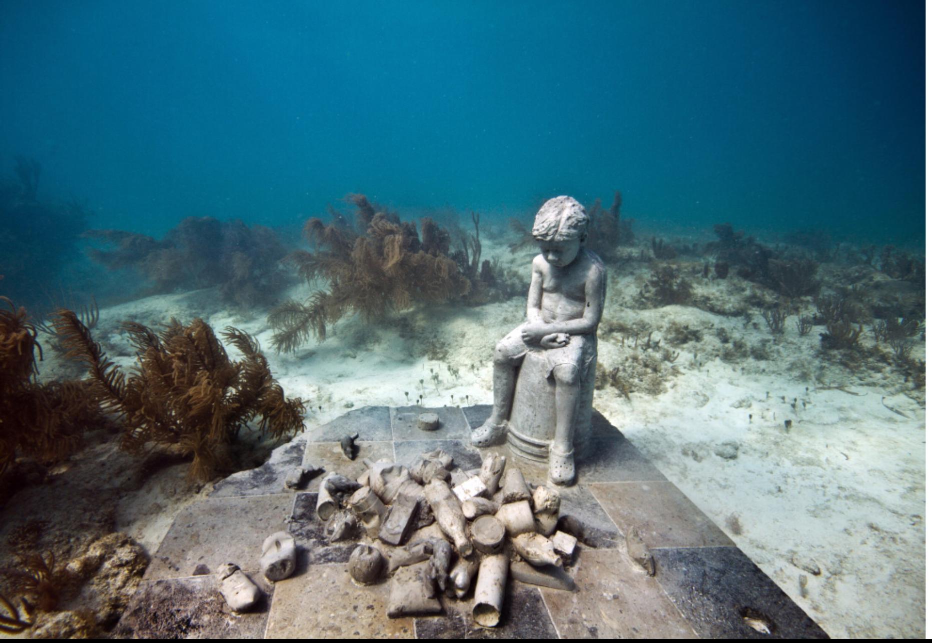 underwater sculpture boy sitting looking at trash on ground