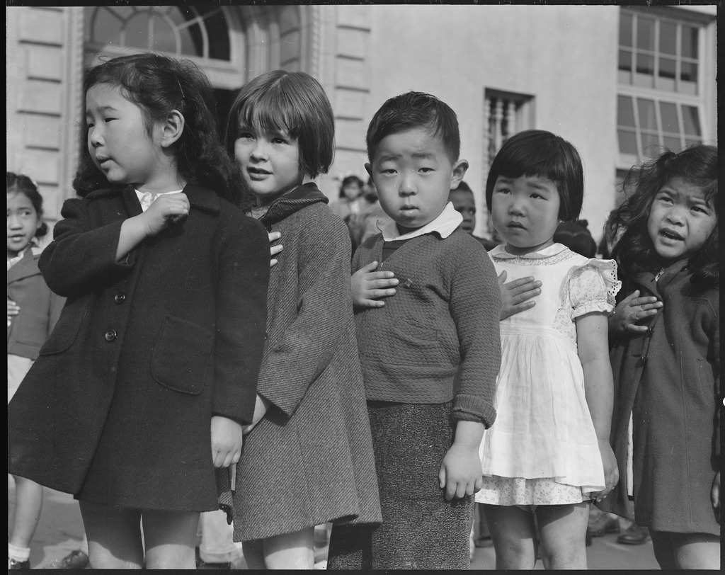 This scene shows first-graders of Japanese ancestry during flag pledge ceremony. They stand in a line and hold a hand to their heart.