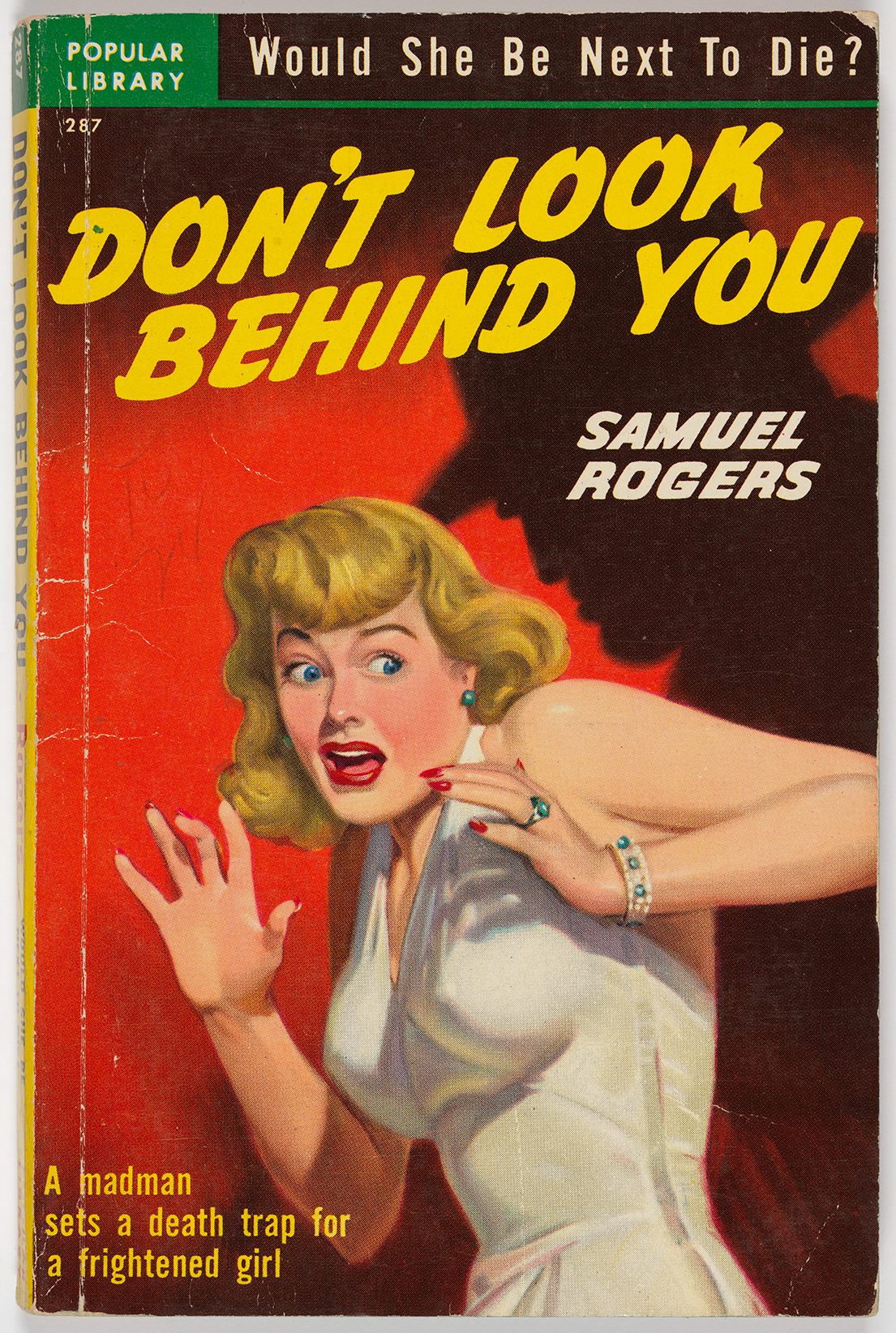 "This novel from Samuel Rogers was published by Popular Library with the tagline, ""Would she be next to die?"" The plot is described as follows: ""A madman sets a deathtrap for a frightened girl."" A blonde woman wearing a white dress holds up her hands in fear, and a dark shadow of a frowning man a hat appears on a red background behind her. The woman has bright red nails and jewelry that matches her blue eyes, and her hair is carefully coiffed."