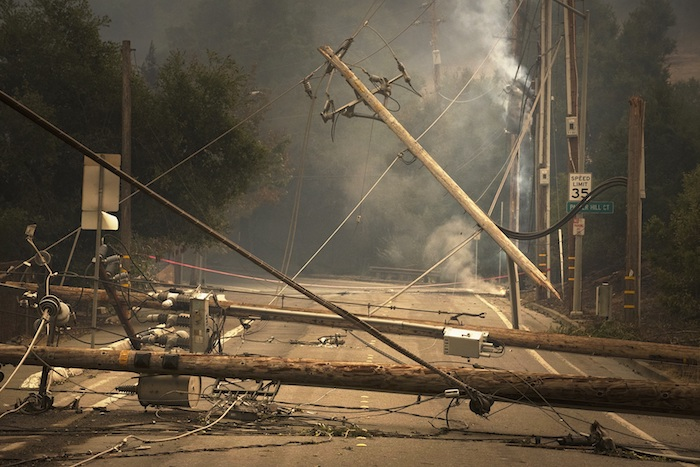 smoke and downed telephone poles across a road