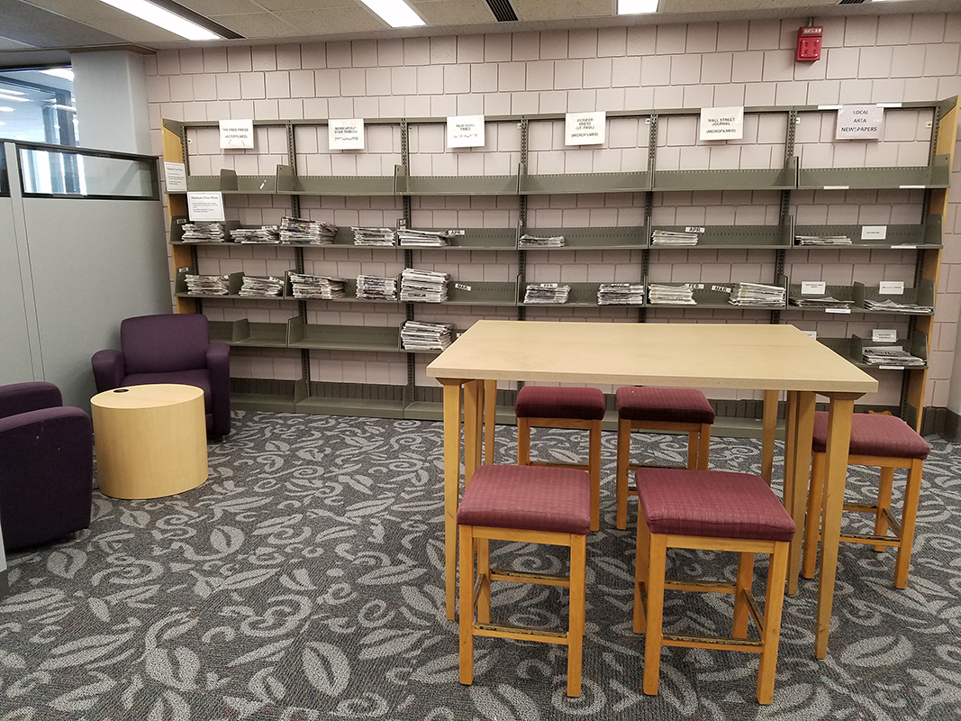 the newspaper area has shelves of current newspapers organized by date along with tables and chairs