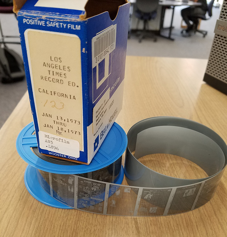 an example of microfilm on a reel and the box it comes in