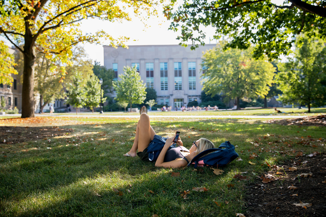 A student relaxes on the Ag Quad in fall.