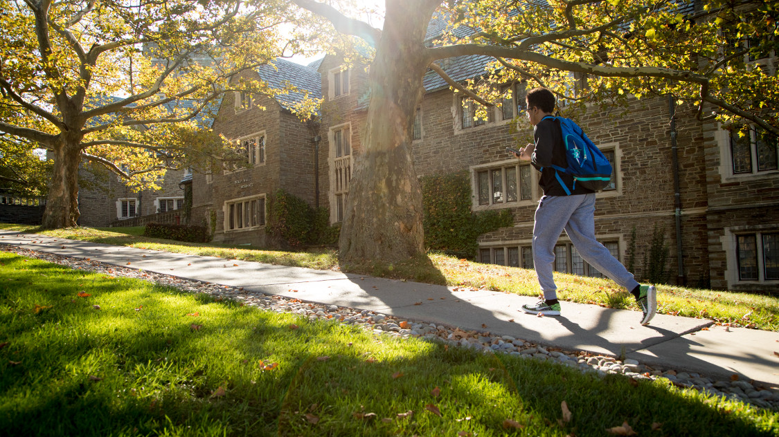 A student walks past Boldt Hall in fall.