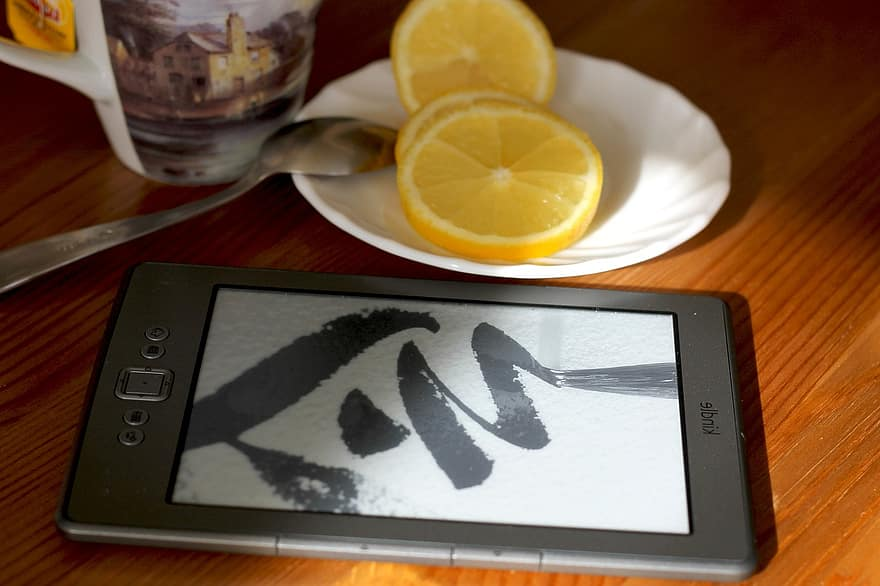 ereader device on table next to cup of tea