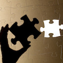 Shadow of hand with puzzle piece - Britannica ImageQuest