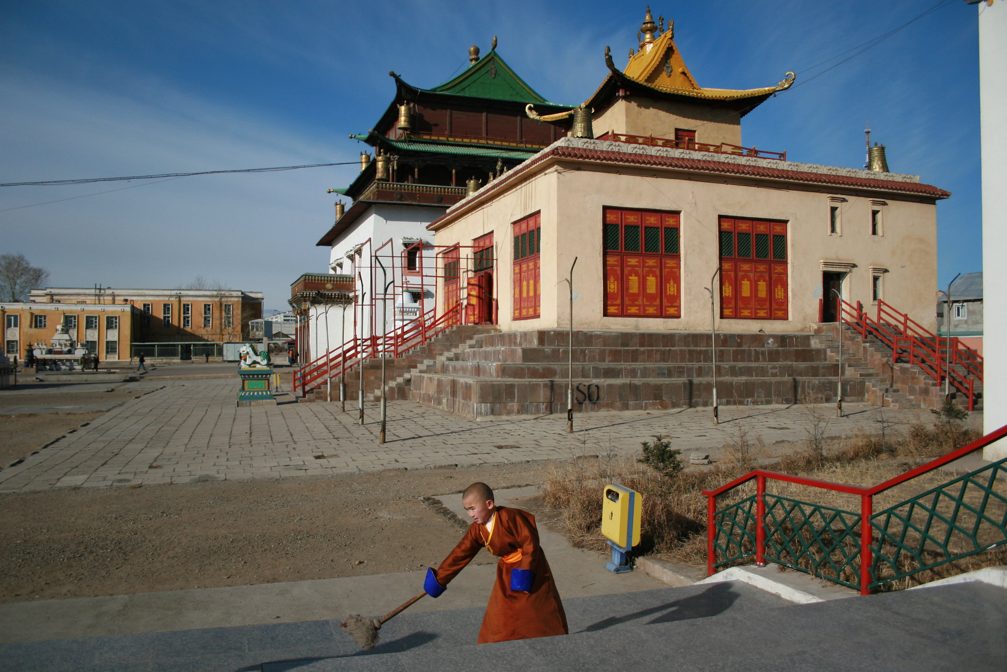 Boy sweeps monastery stairs at Gandan Khiid in Ulaanbaatar