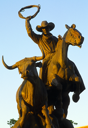 Bronze sculpture of cowboy with lasso and steer.