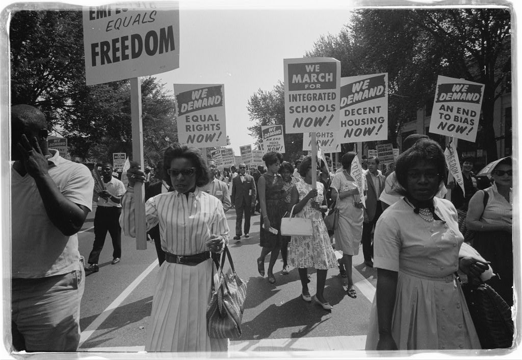 Black and white photograph of march particpants holding signs that call for equal rights. Two African American women are in the foreground.