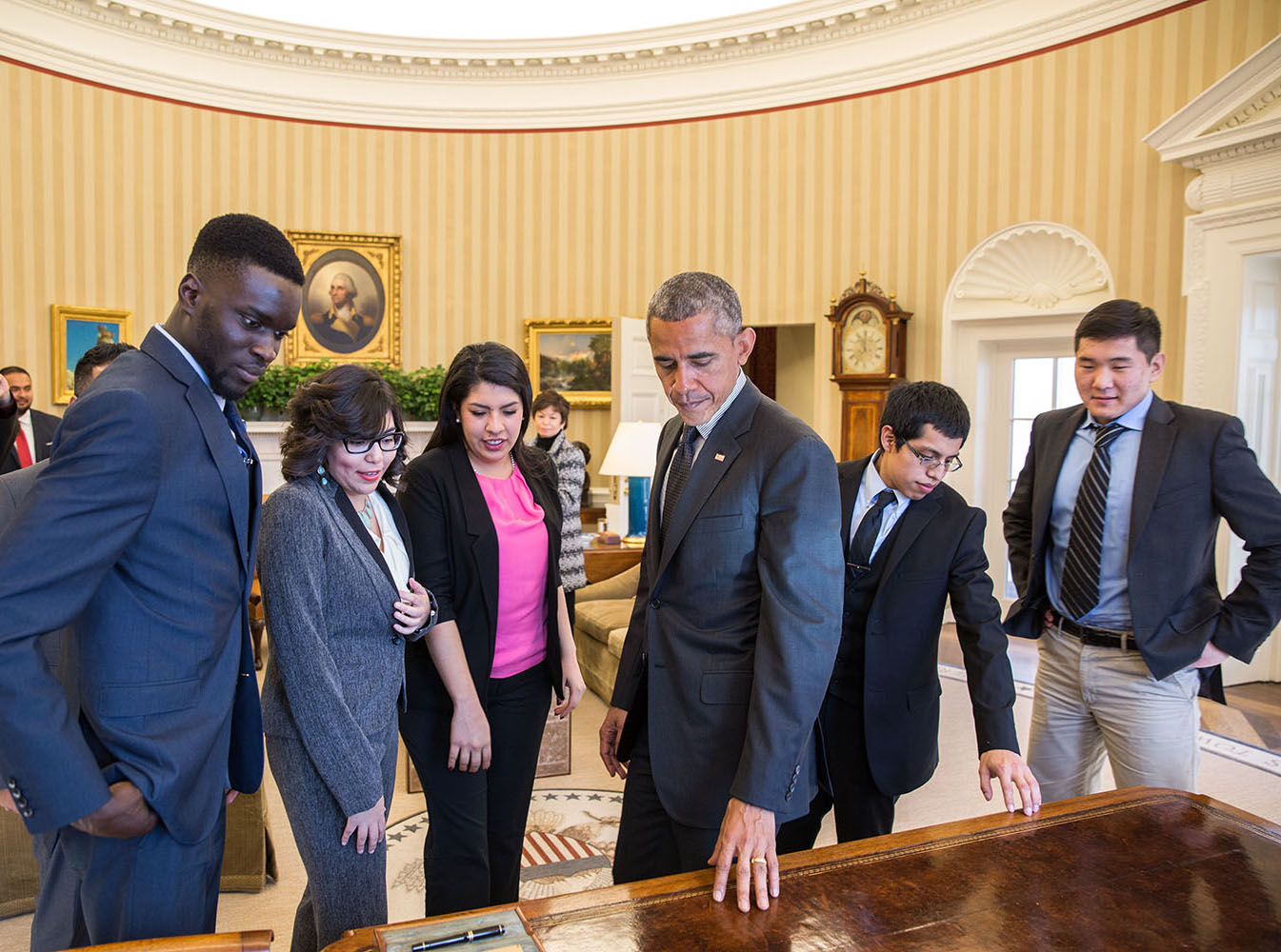 Obama shows DREAMers around Oval Office.