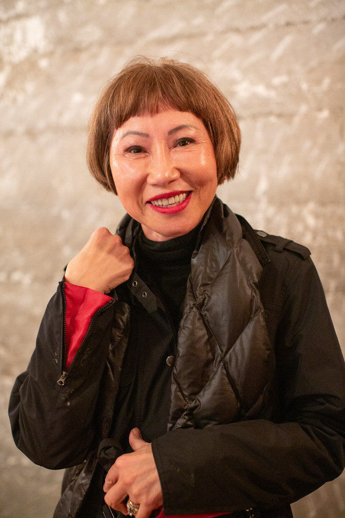 Amy Tan, a smiling Asian woman in a black shirt and insulated vest faces the camera